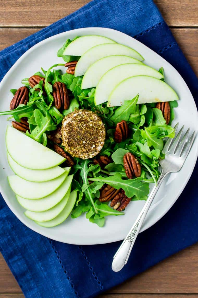 Overhead image of a white plate with a salad, pecans, and apple slices and a fork and dark blue napkin all on a wood backdrop