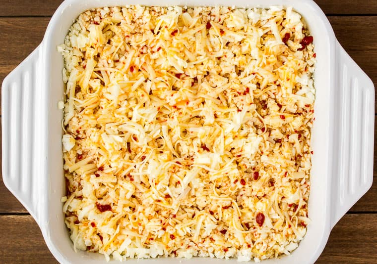 Close up overhead view of the egg mixture mixed in with the cauliflower rice and cheese in a white baking dish on a wood background