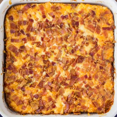A Baked Keto Breakfast Casserole in a white square baking dish on a wood background with a dark blue napkin