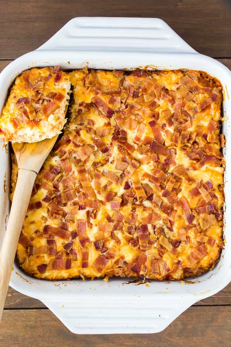 Overhead view of a breakfast casserole in a white square baking dish with a wooden spoon lifting out a scoop on a wood background