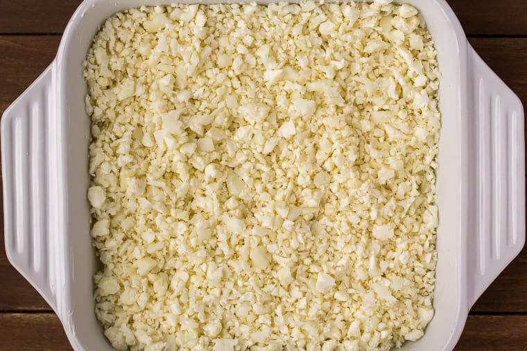 Close Up Overhead of Rice Cauliflower in a Baking Dish with a wood background