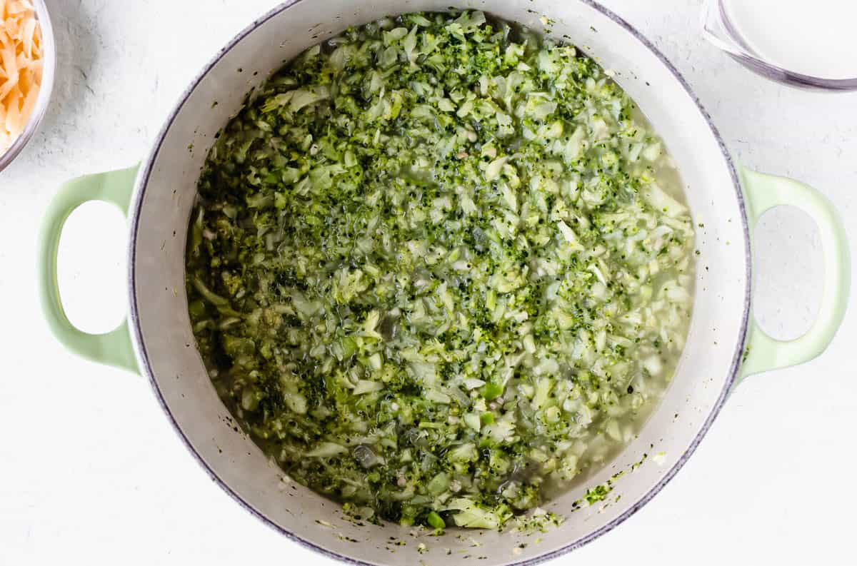 Riced broccoli cooking in a Dutch oven over a white background