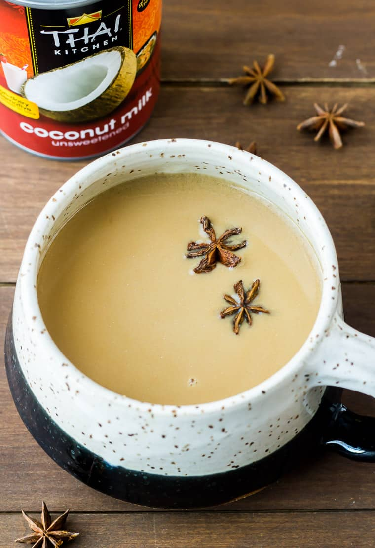 A Mug of Coconut Chai Tea Latte with Star Anise in it and Around it and a Can of Coconut Milk all on a Wood Background