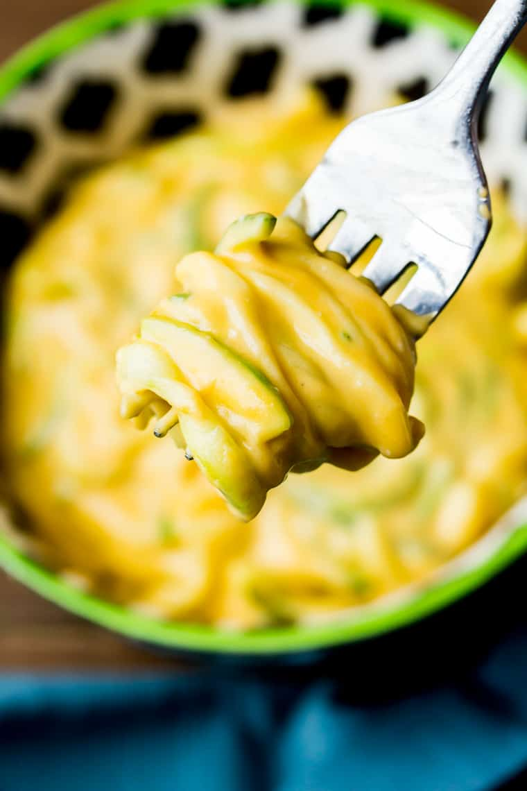 A fork with zucchini mac and cheese wrapped around it hovering over a black, white, and green bowl