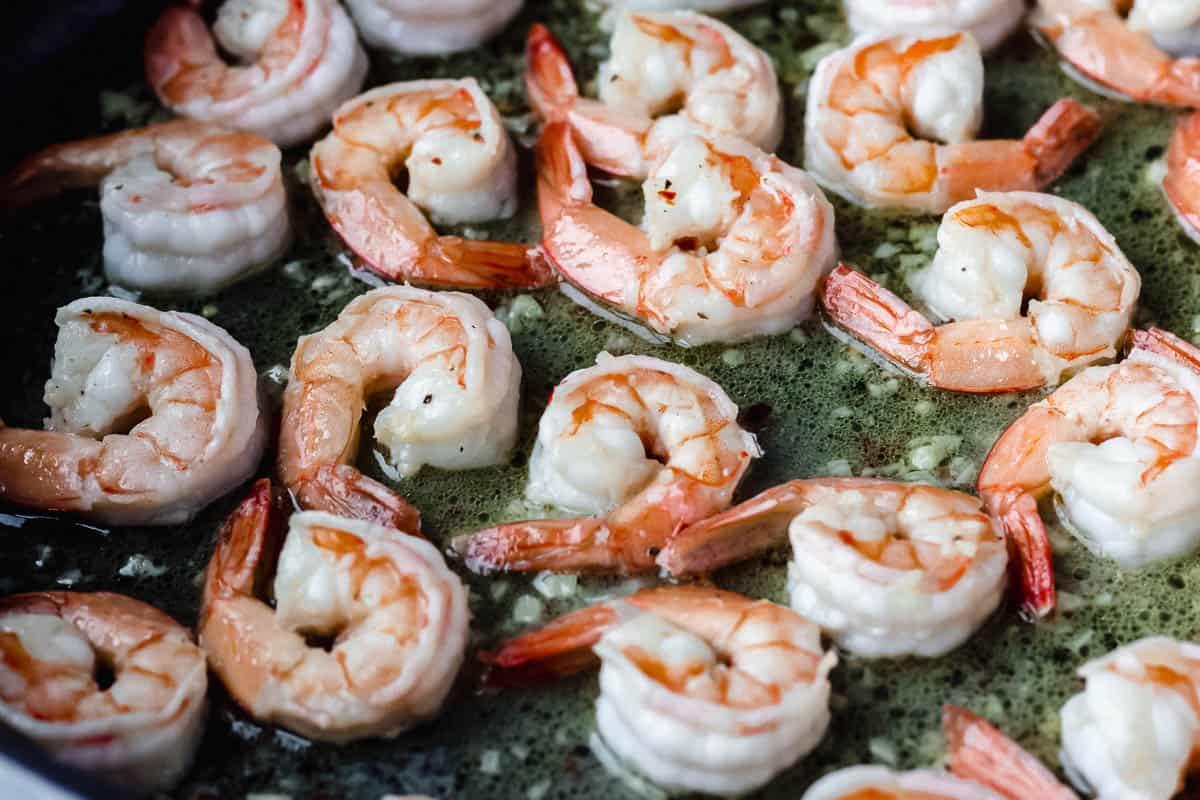 Shrimp cooking in a garlic butter sauce in a black skillet