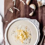 a bowl of white cheddar cauliflower soup with text overlay
