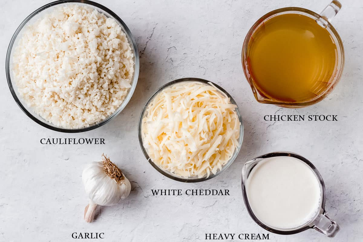 Ingredients to make white cheddar cauliflower soup on a white background with labels