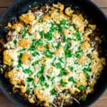 Italian Ground Beef and Cauliflower in a Black Skillet topped with melted mozzarella cheese and fresh parsley on a wood background