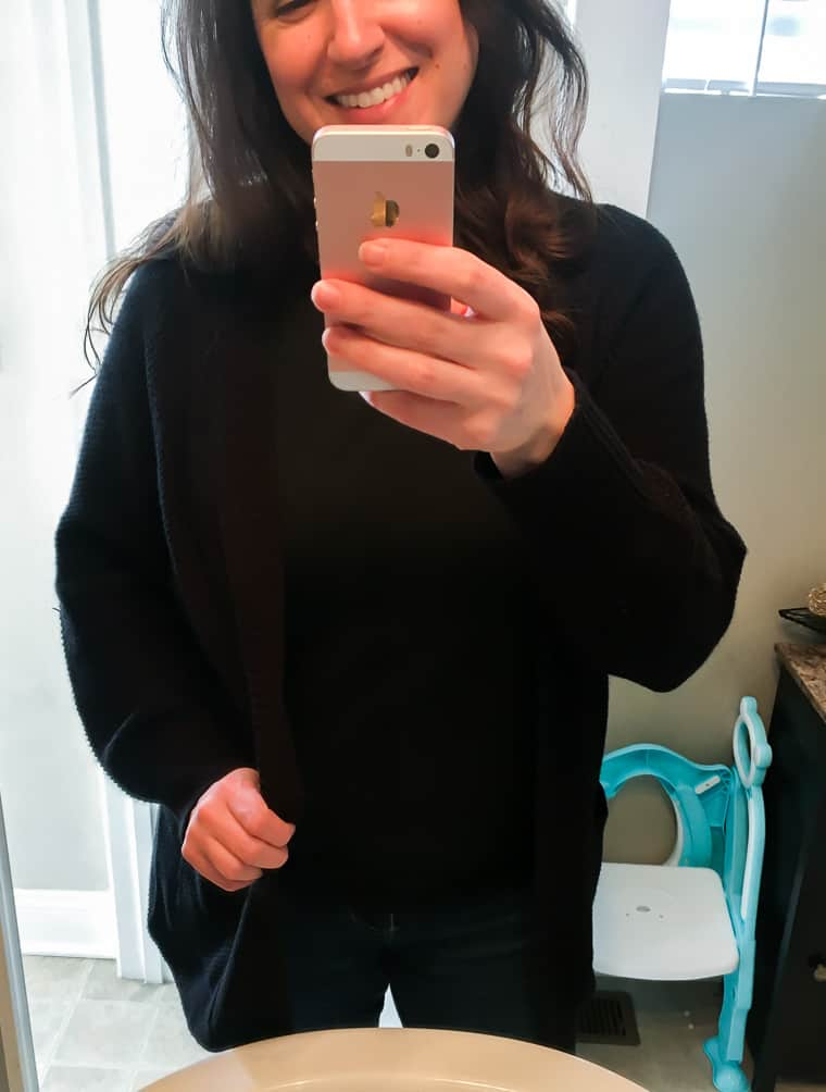 A girl wearing a black shirt and cardigan standing in front of a mirror