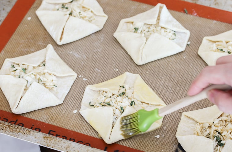 Puff Pastry squares topped with cheese with corners folded over being brushed with egg wash with a green silicone brush on a silpat mat