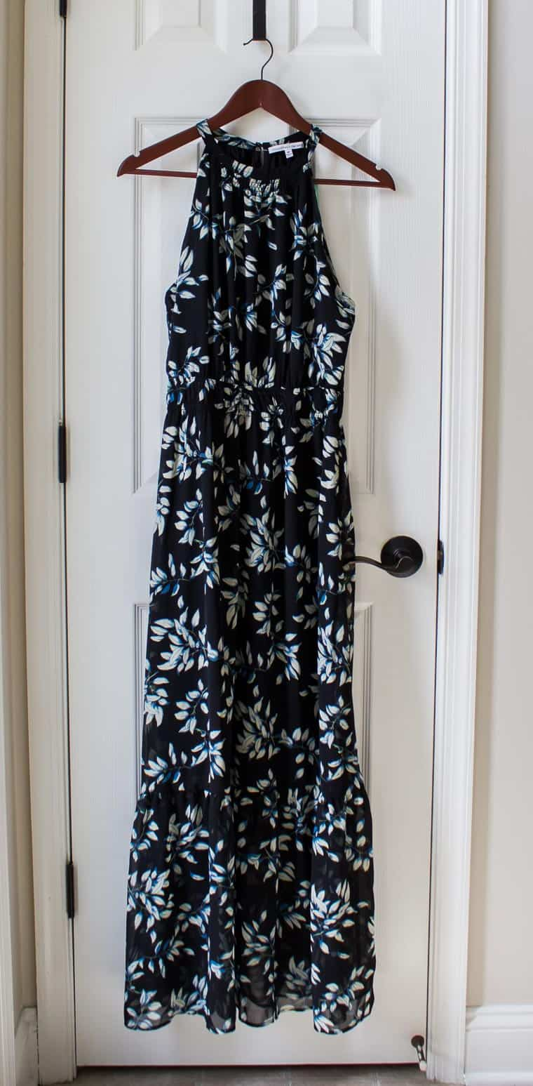 Collective Concepts Signa Maxi Dress in black with a blue floral print on a hanger over a white door
