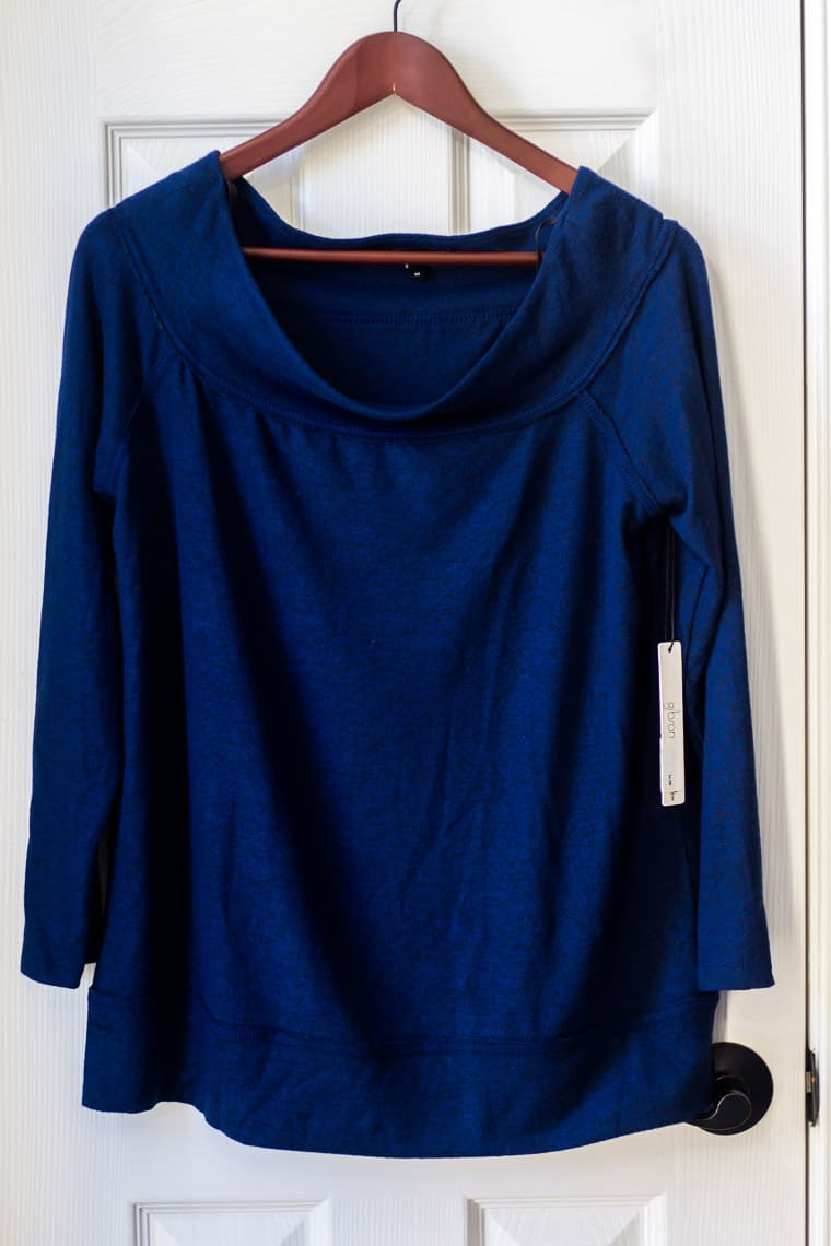 Gibson x Living in Yellow Mary Fleece Off the Shoulder Top in Navy on a hanger on a white door