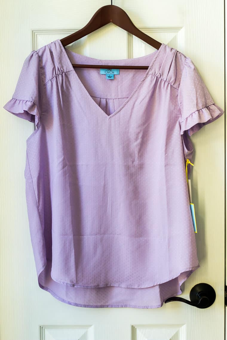 CeCe Ruffled Satin Jacquard Top in Soft Orchid on a hanger on a white door