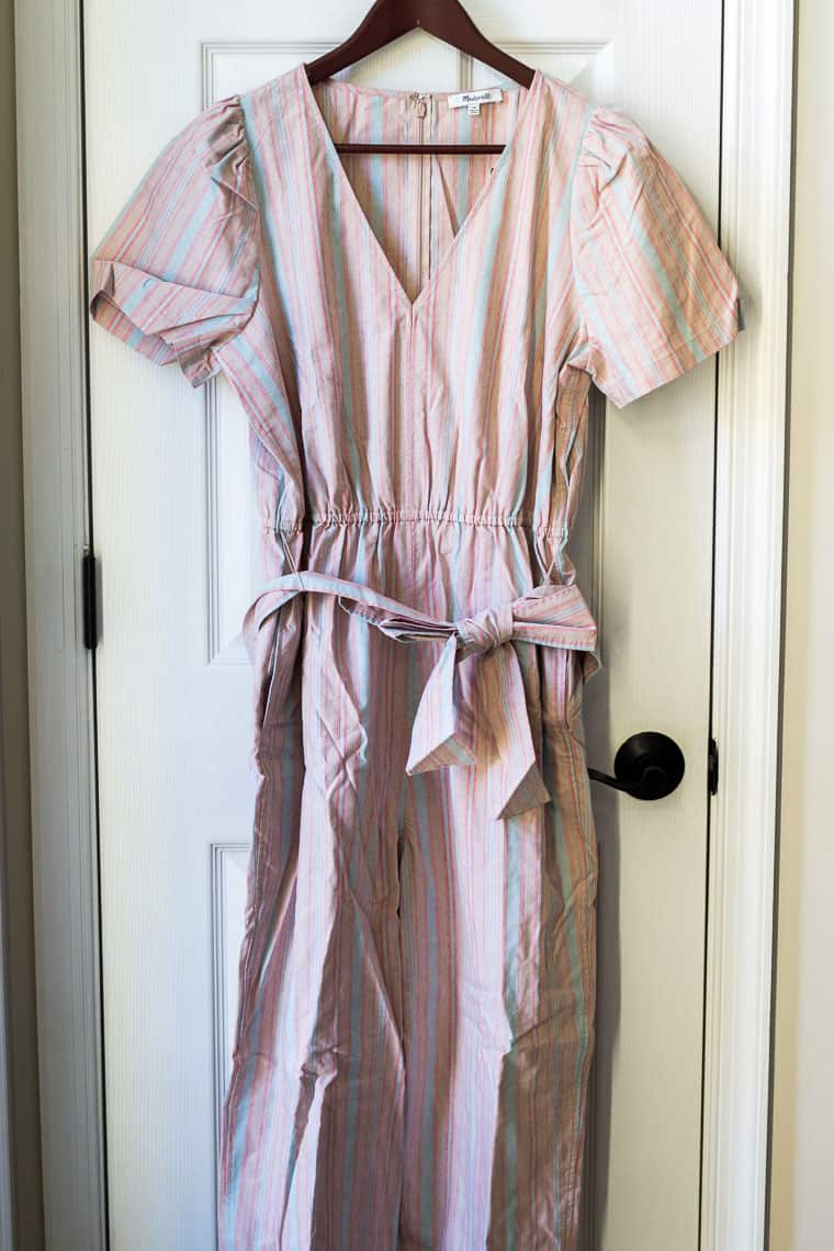 Madewell Puff Sleeve Tampered Jumpsuit in Blue on a hanger on a white door