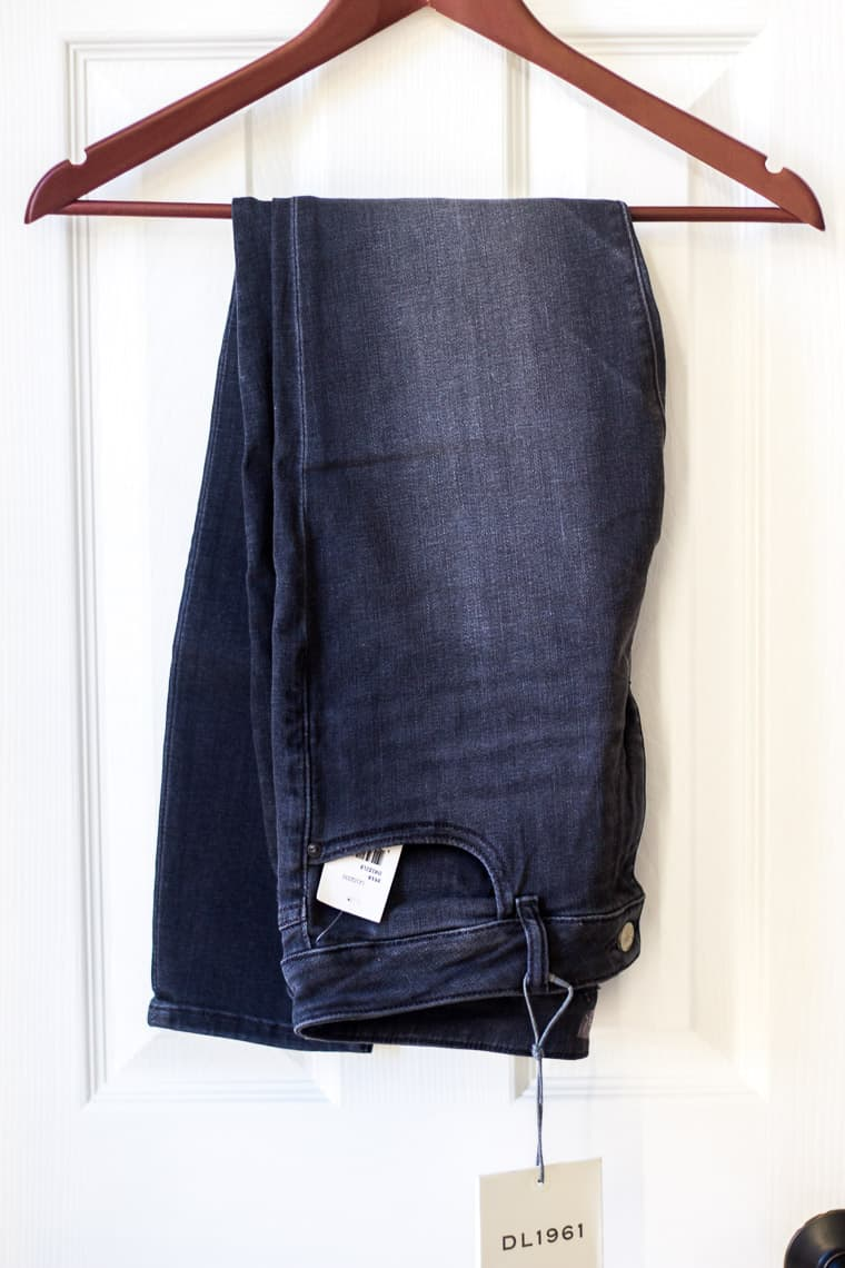 DL1961 Florence Instasculpt Ankle Skinny Jeans in Drizzle dark gray on a hanger over a white door