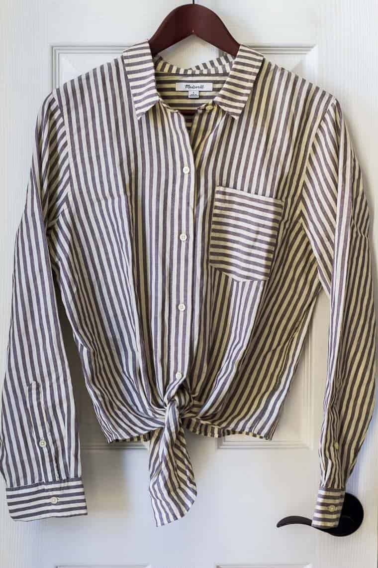 Madewell Maitland Stripe Tie-Front Shirt in Dark Eggplant on a hanger on a white door