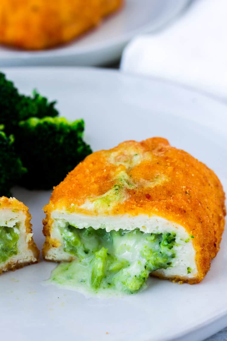 A breaded chicken breasts cut open to reveal a broccoli and cheese filling, on a white plate with a side of fresh broccoli