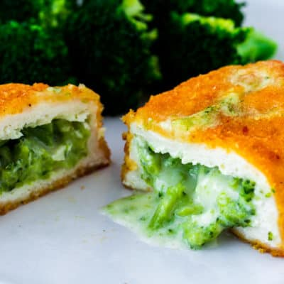 A close up image of a chicken breast on a white plate cut open to reveal the broccoli and cheese inside with broccoli in the background