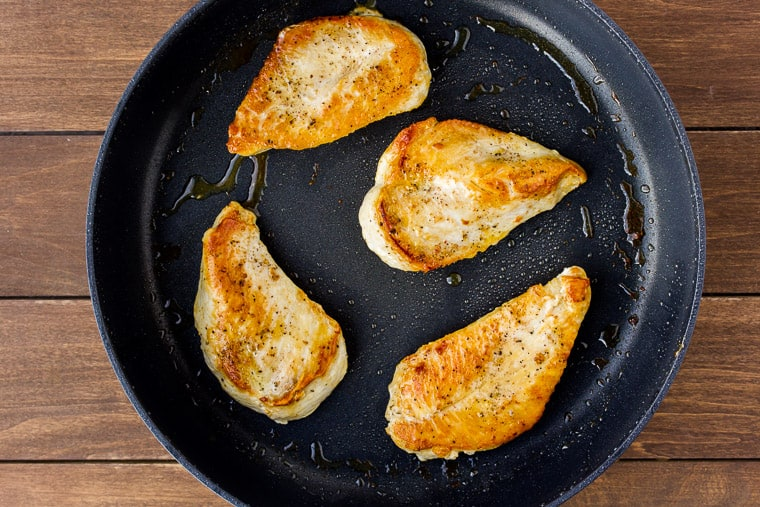 4 chicken breasts cooking in oil in a black skillet on a wood backdrop