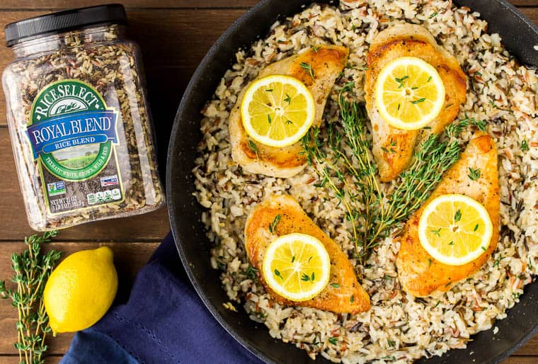 A black skillet with Creamy Lemon Chicken and Rice in it with a container of rice, a lemon, and fresh thyme next to it as well as a dark blue napkin over a wood backdrop