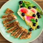 Sumac Chicken cut in slices on a green plate with a side of roasted cabbage topped with radishes and blueberries. There is a gray napkin and fork on the side on a wood backdrop.