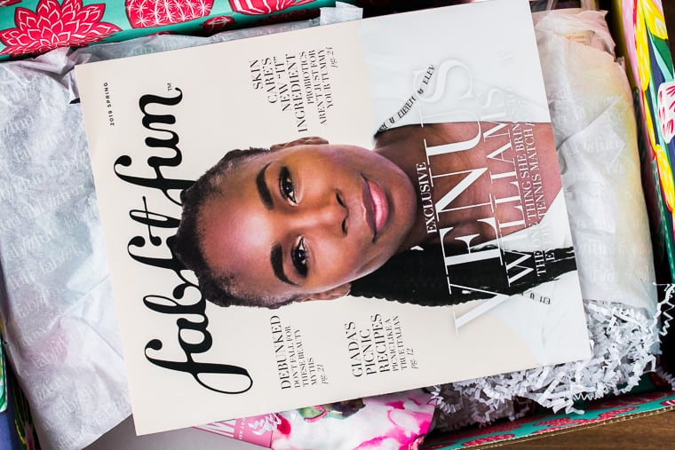 Opened FabFitFun box with magazine on top and tissue paper and items underneath