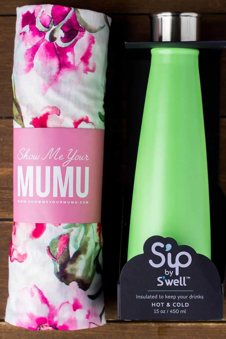 Show Me Your Mumy Floral Robe rolled up and a green water bottle on a wood backdrop