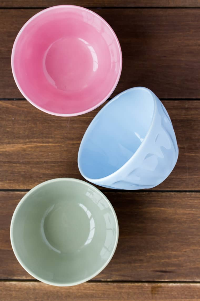 3 pastel colored ceramic prep bowls on a wood backdrop