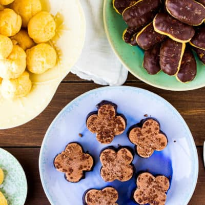 Cream puffs, mini eclairs, and chocolate mousse on pastel plates with forks, small dessert plates and a white napkin - all over a wood backdrop