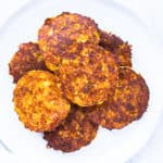 Cauliflower Hash Browns on a white plate over a white background