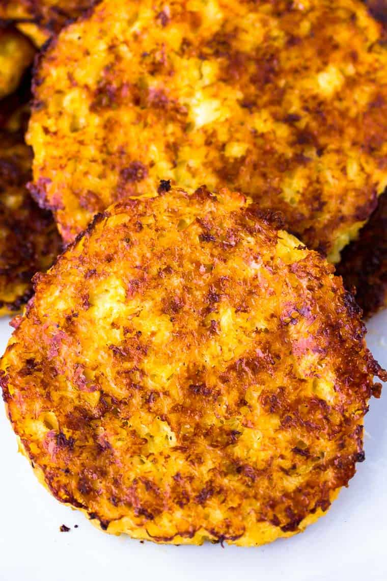 Close up of 2 Cauliflower Hash Browns on a white background