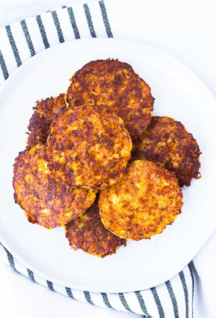A white plate full of round cauliflower hash browns over a black and white striped dish towel over a white background