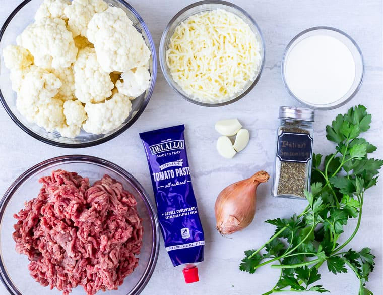 Ingredients to make low carb ground beef and cauliflower skillet on a white background