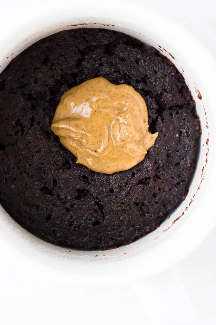 Dark Chocolate cake topped with a dollop of almond butter in a white mug over a white background