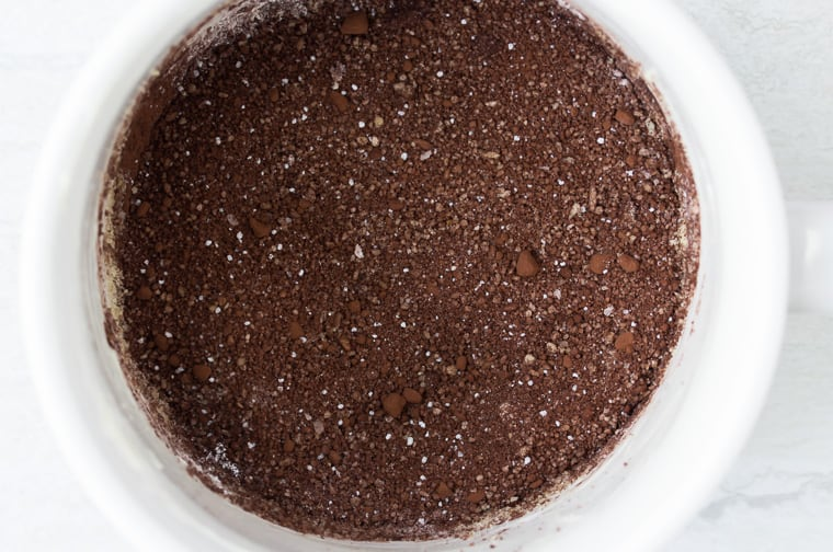 Dry ingredients for a chocolate cake in a white mug over a white background