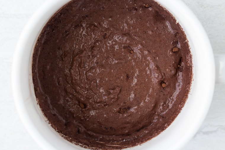 Chocolate cake batter in a white mug over a white background