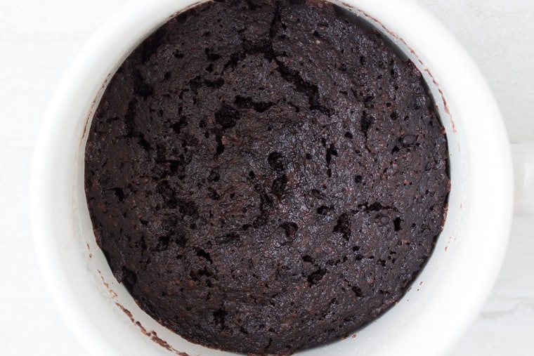 Cooked dark chocolate mug cake in a white mug over a white background