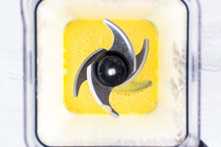 Overhead view of a blender with ingredients for hollandaise sauce in it