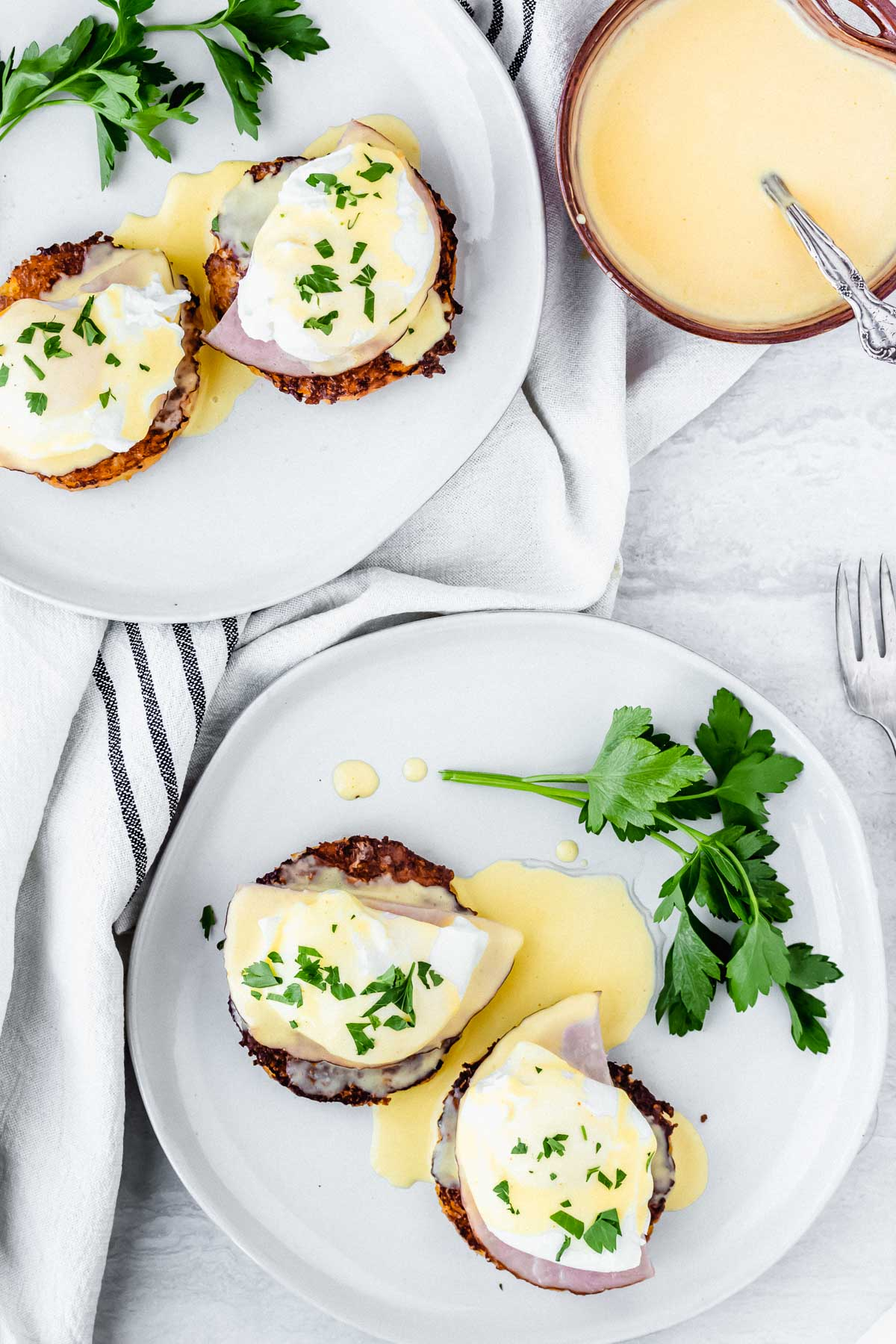 overhead of two plates of keto eggs benedict with a towel between them and a bowl of hollandaise sauce next to them