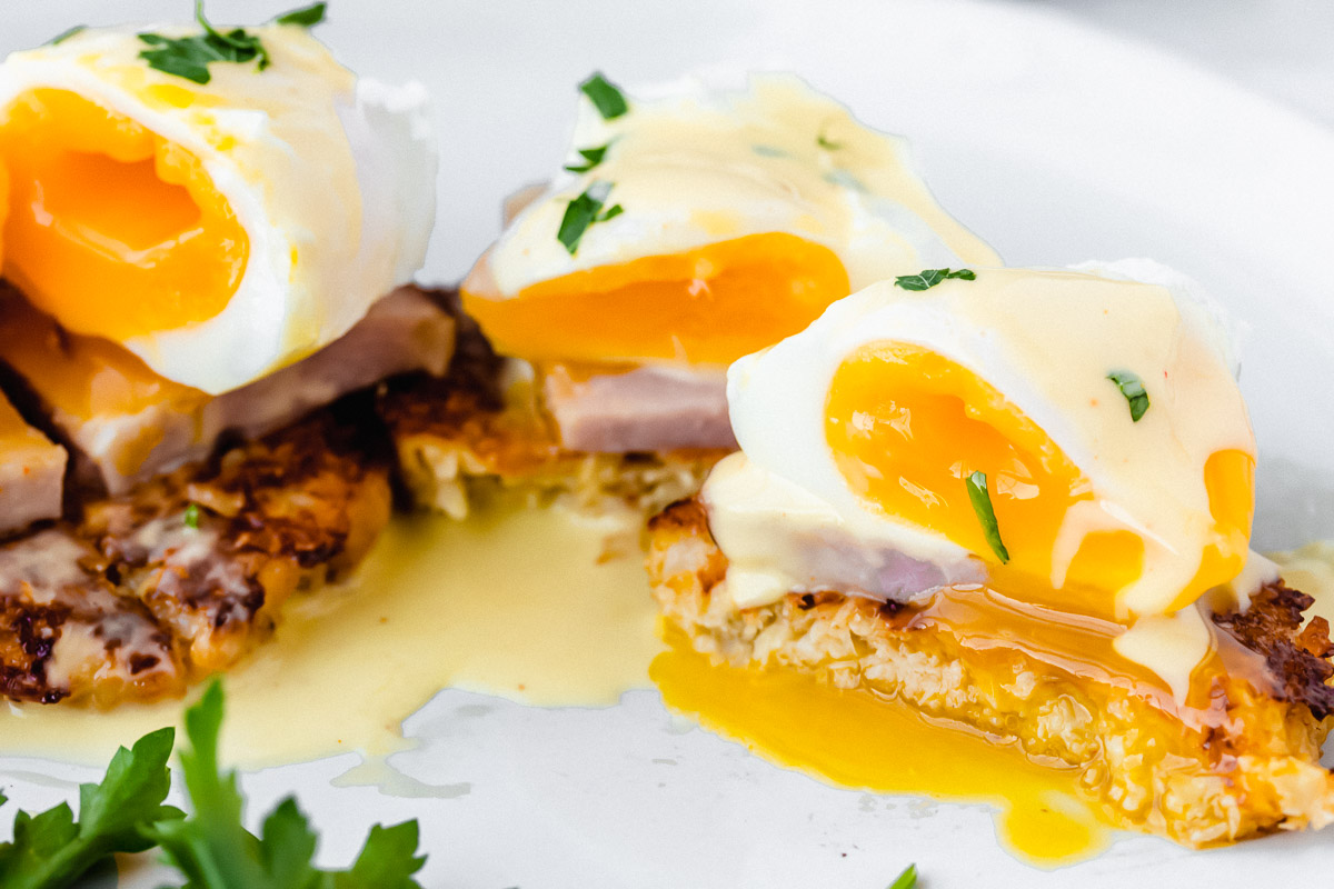 Keto eggs benedict cut open so the egg yolk is running out on a white plate