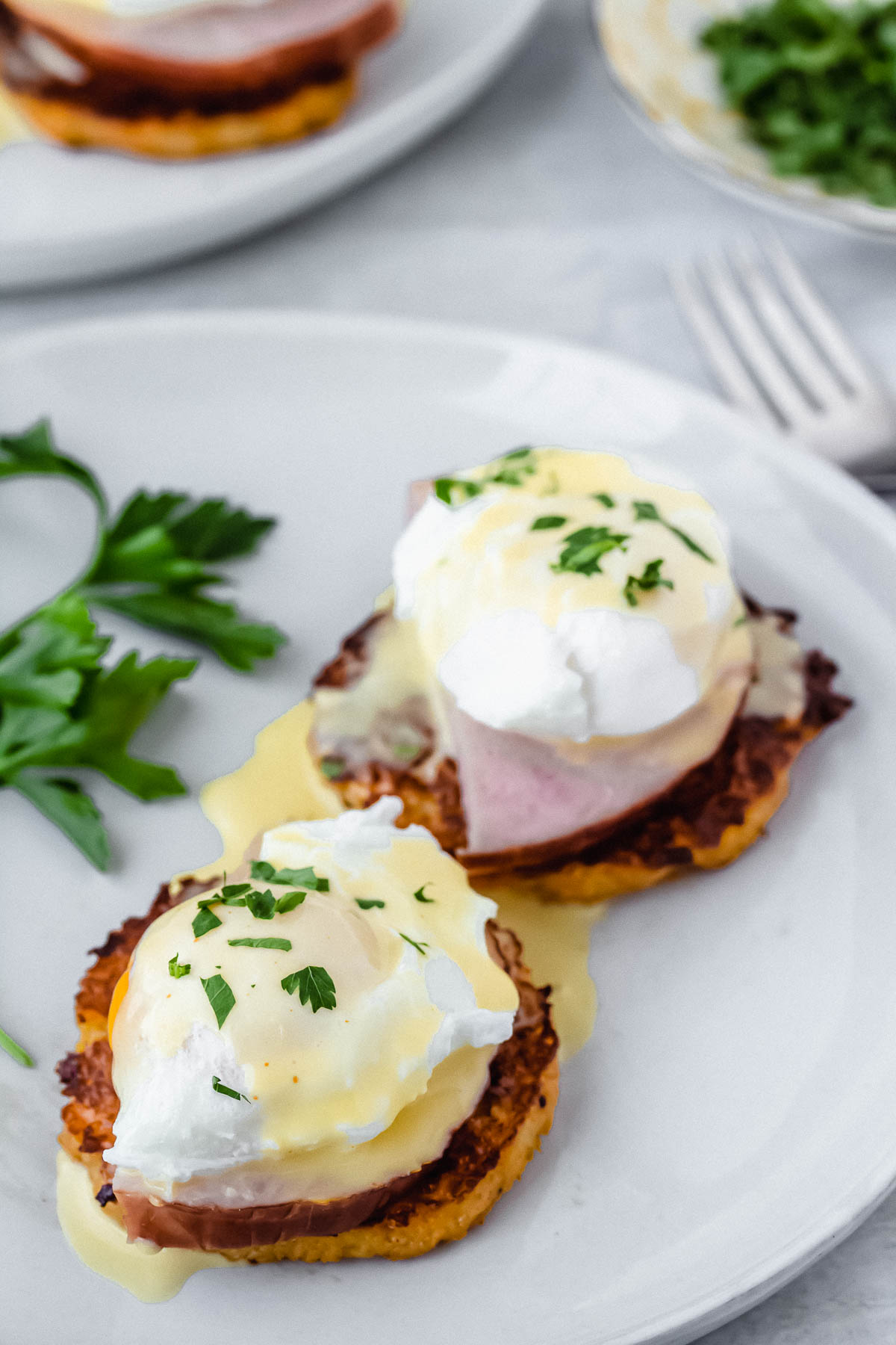 Keto eggs benedict on cauliflower toasts on a white plate with a second plate and fork in the background
