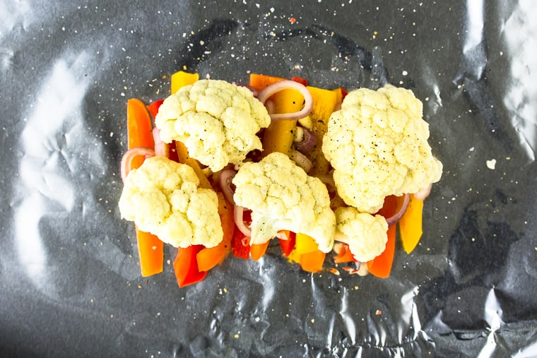 Pepper strips topped with cauliflower florets laid out on a piece of foil