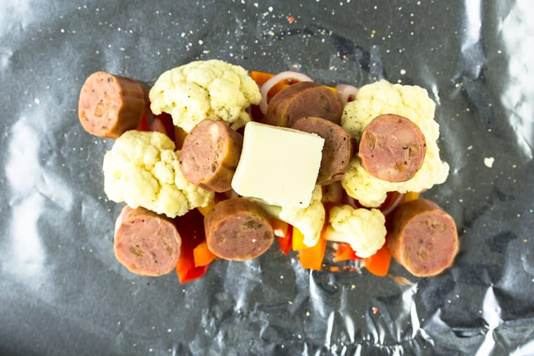 sausage, cauliflower, peppers and butter on a foil sheet