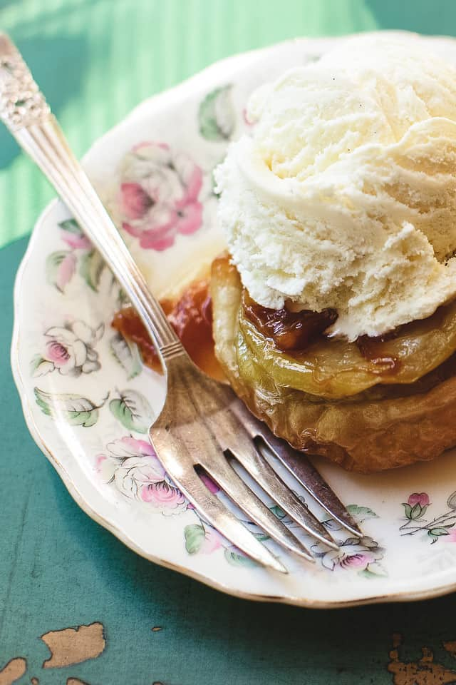 Close up on an apple tarte tatin on a floral plate with a fork and topped with ice cream