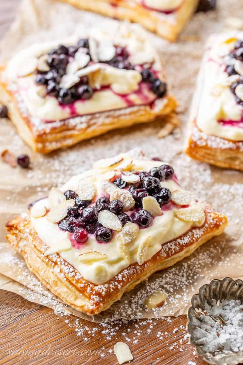 Blueberry Puff Pastry Tarts spread out on parchment paper and covered in powdered sugar