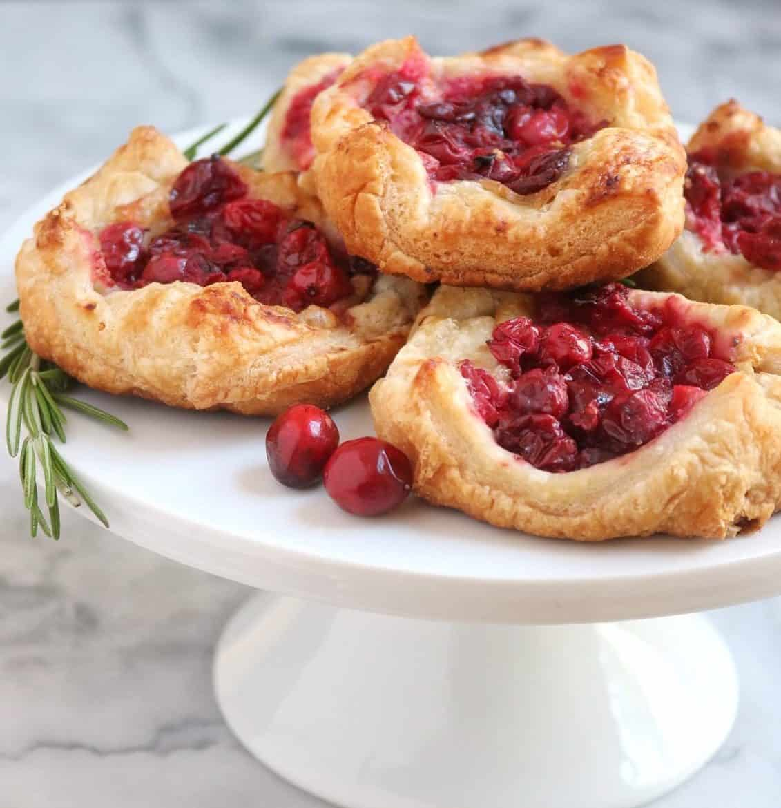 Cranberry Brie Tarts on a white cake platter with rosemary and fresh cranberries on a marble backdrop
