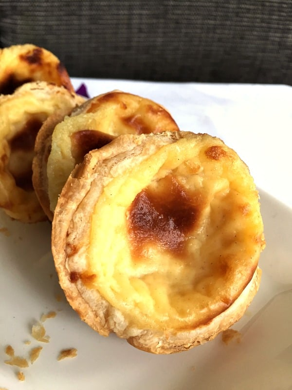 Portuguese Custard Tarts also known as Pastéis de Nata close up on a white dish with a gray background
