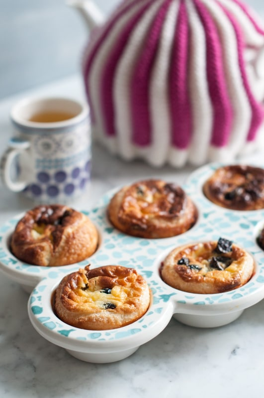 Custard Tarts with Prunes in a Baking Dish with a cup of tea and purple and white striped tea pot in the background