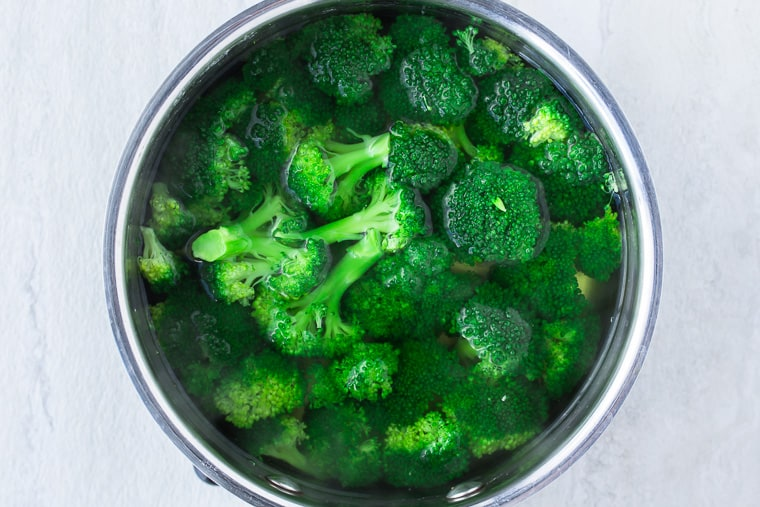 Broccoli boiling in water in a silver saucepan over a white background