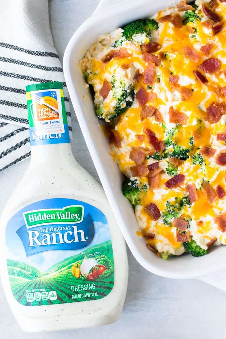 a bottle of ranch dressing next to a white casserole dish with a cheesy broccoli meal in it and a white and black striped dish towel on a white background